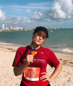 Woman poses with medal for completing 5k