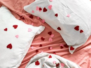 Pillows on a bed with pink sheets and confetti hearts strewn across them