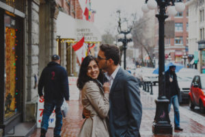 Man kisses wife on cheek on sidewalk in Gastown