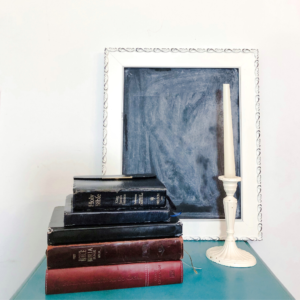 5 Bibles stacked with candle stick next to it black board frame in background