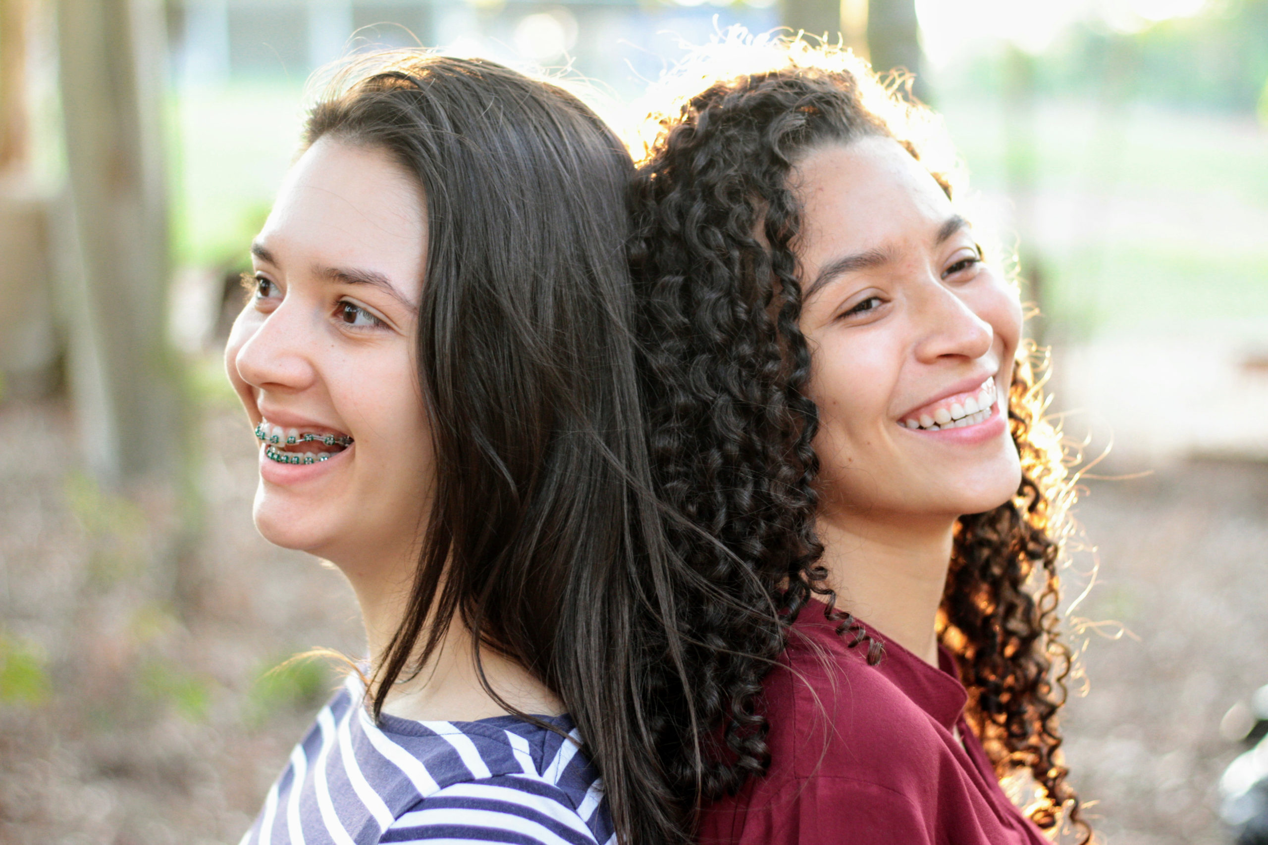 Two women stand back to back looking out of frame and smiling