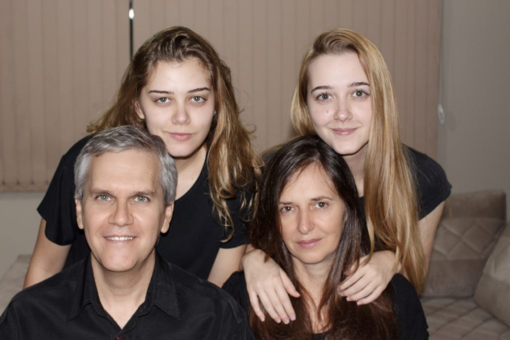 Portrait of a family, husband and wife sit and two grown daughters stand behind them