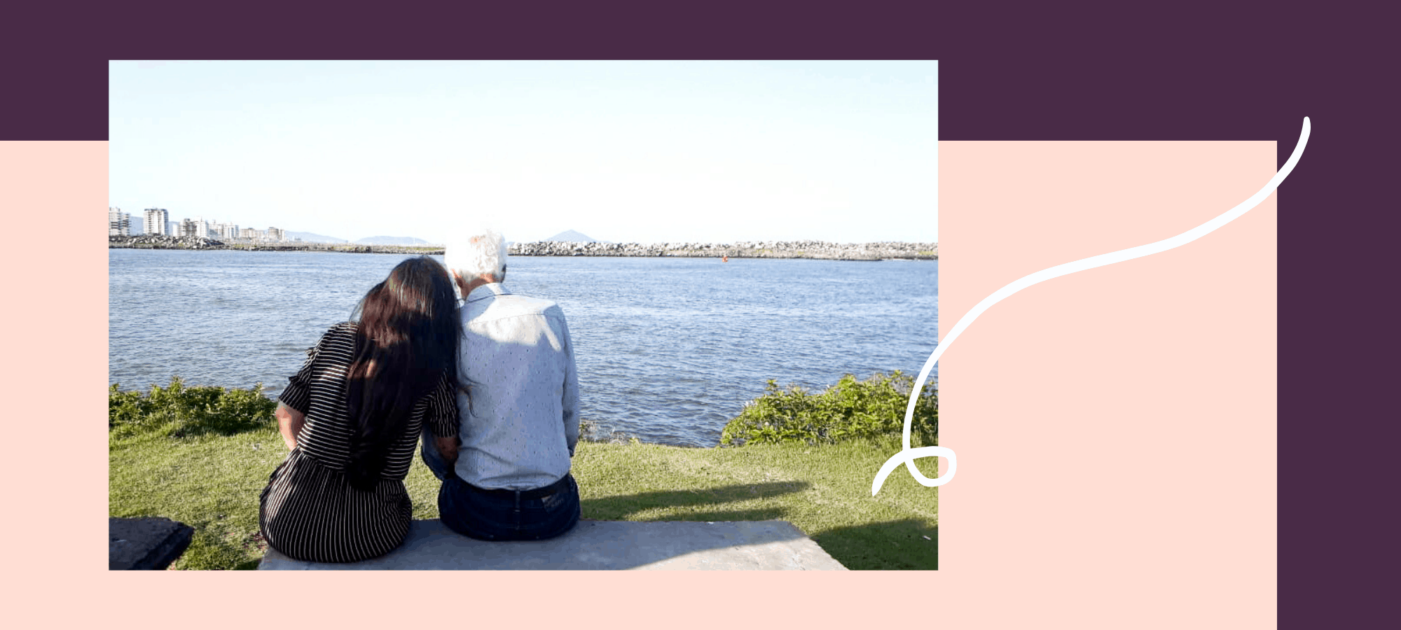 Couple sits on bench overlooking water