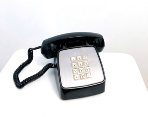 Black telephone and receiver against white background
