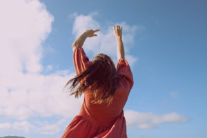Girl twirling hair blowing in the wind against blue sky
