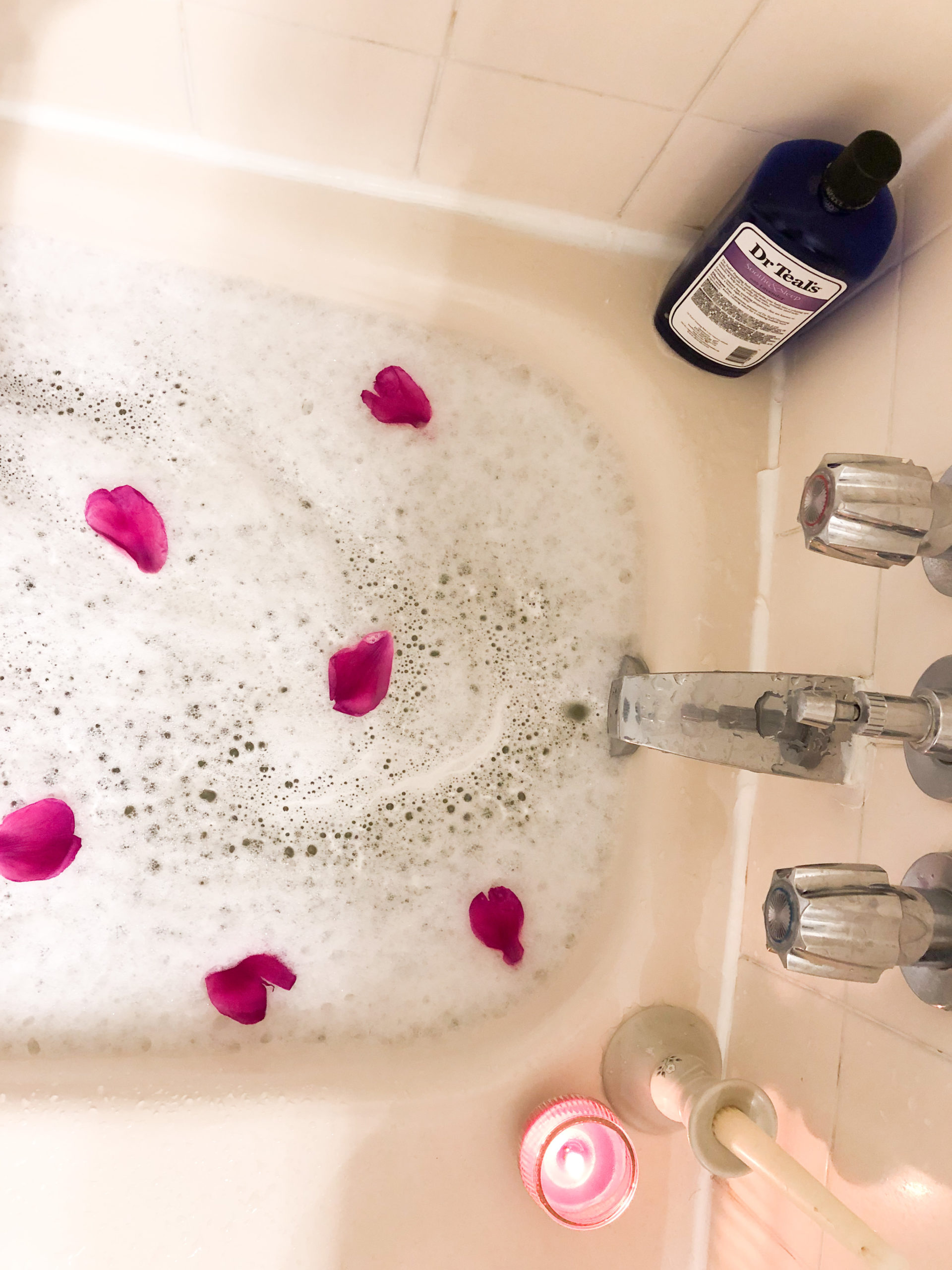 Bubble bath with flower petals and candles