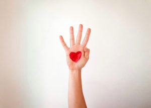 Open palm with red heart draw on hand against white background