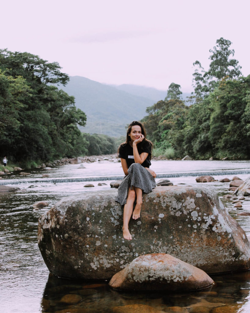 Girl sits on a large rock in middle of a river