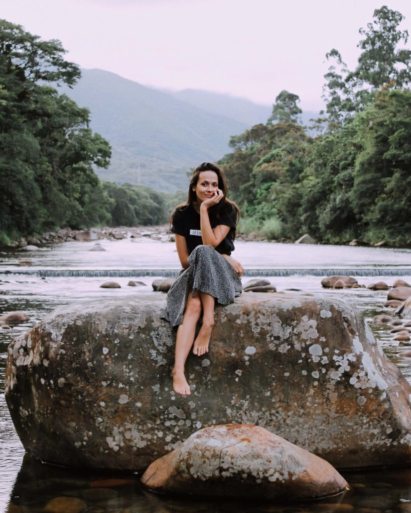 Girl sits on large rock in river