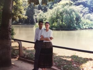 Young couple from the 90s in foreground lake behind them