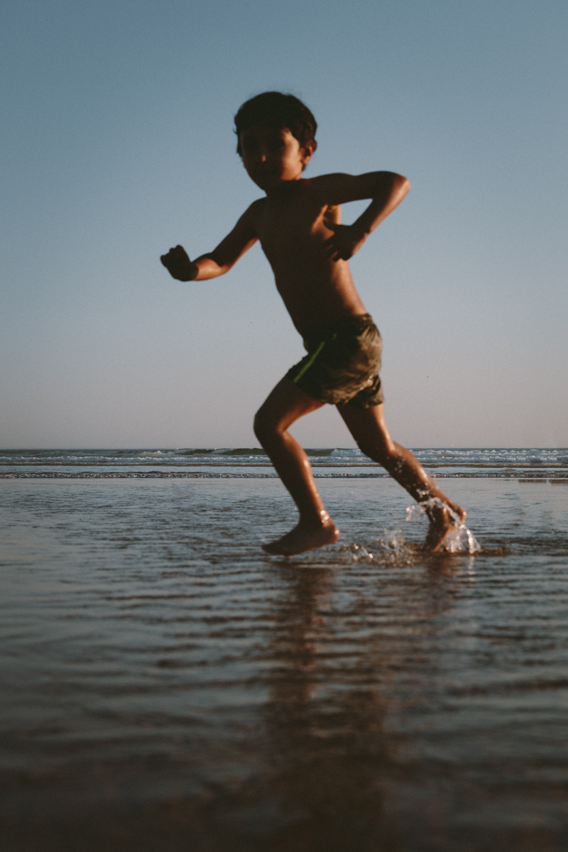 Child runs in sand and ocean water on beach