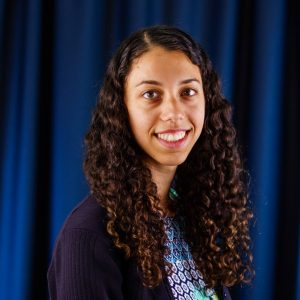 Career Fair Photo of woman with curly hair against blue backdrop