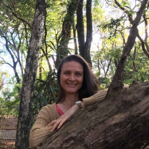 Woman faces camera trees in background