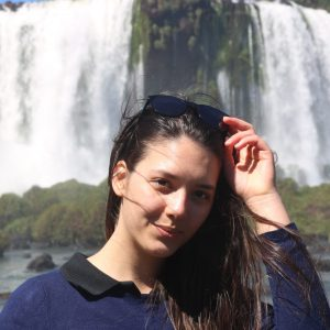 Young woman faces camera waterfalls in background